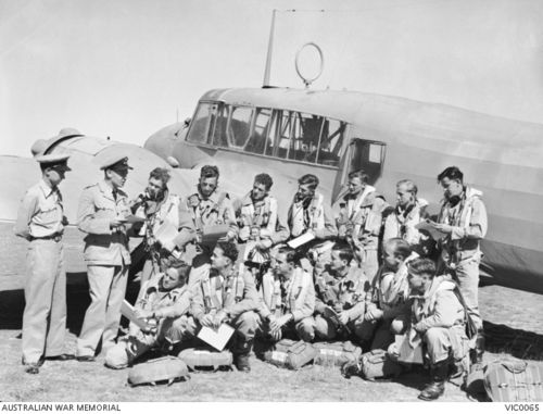RAAF trainees being briefed for an airborne exercise in front of an Avro Anson